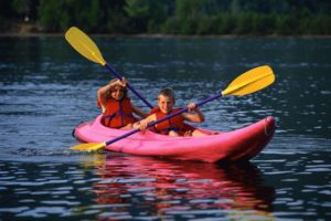 Two children kayaking on a lake